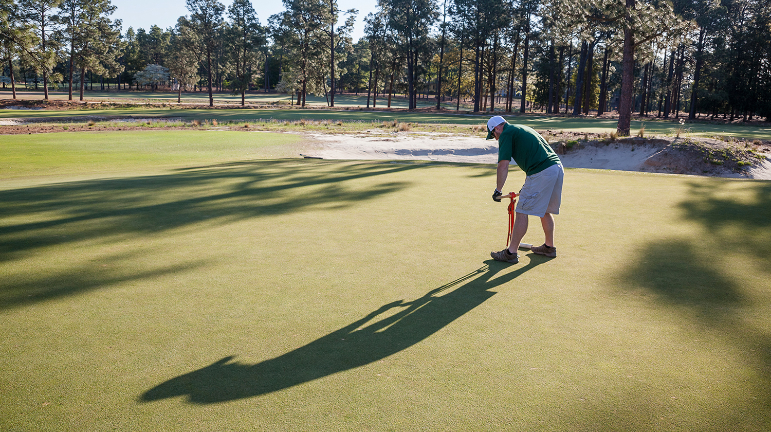 A golf course worker cuts a new hole on a putting green