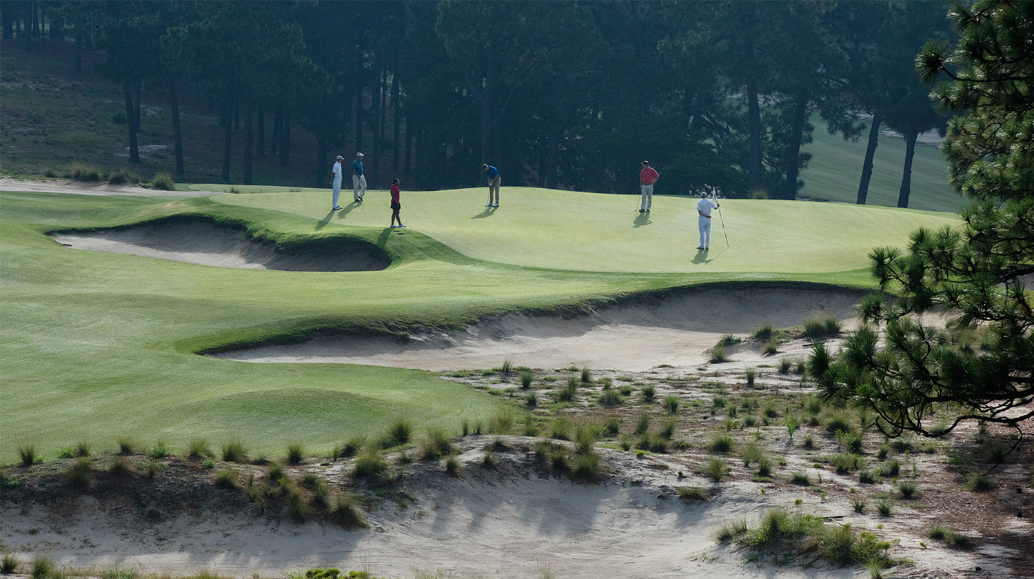 A group of golfers putt on Pinehurst Number 2's green