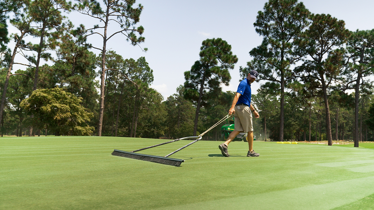 A golf course worker sweeps a putting green