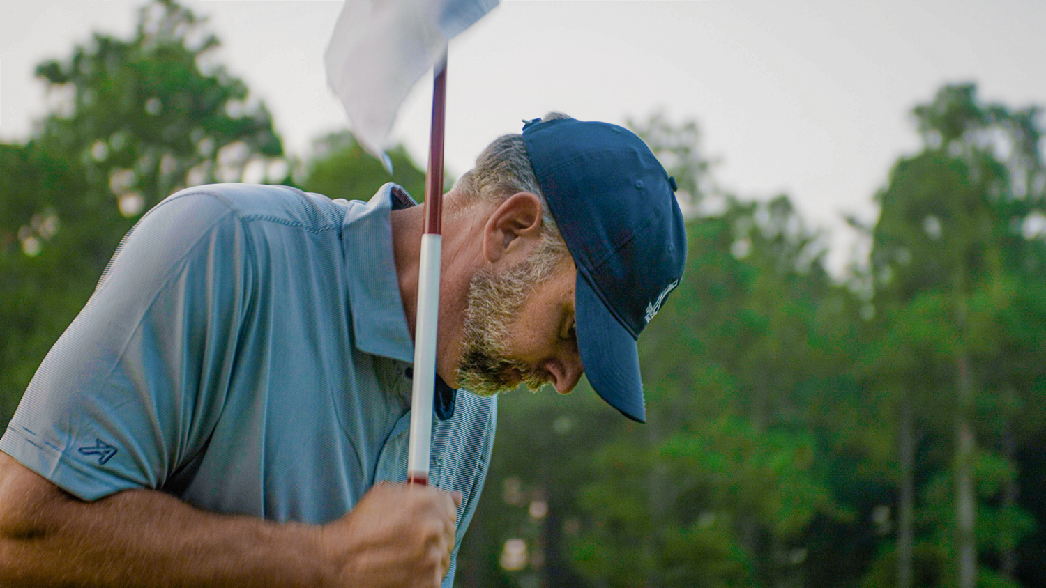 Man in a blue hat plants a golf hole flag