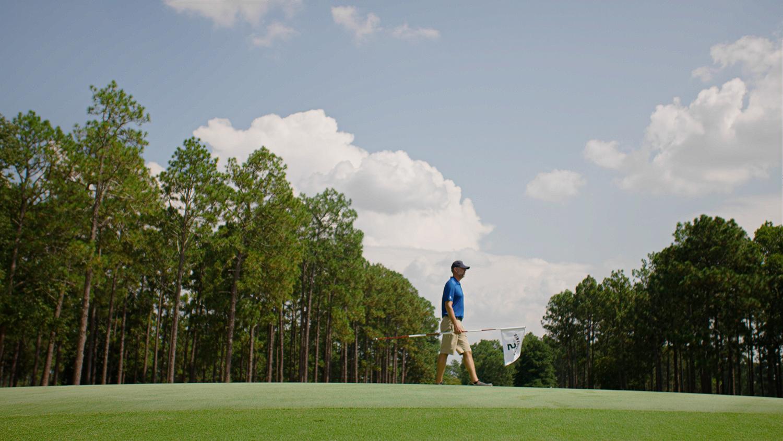 Golf course superintendent walks across a putting green