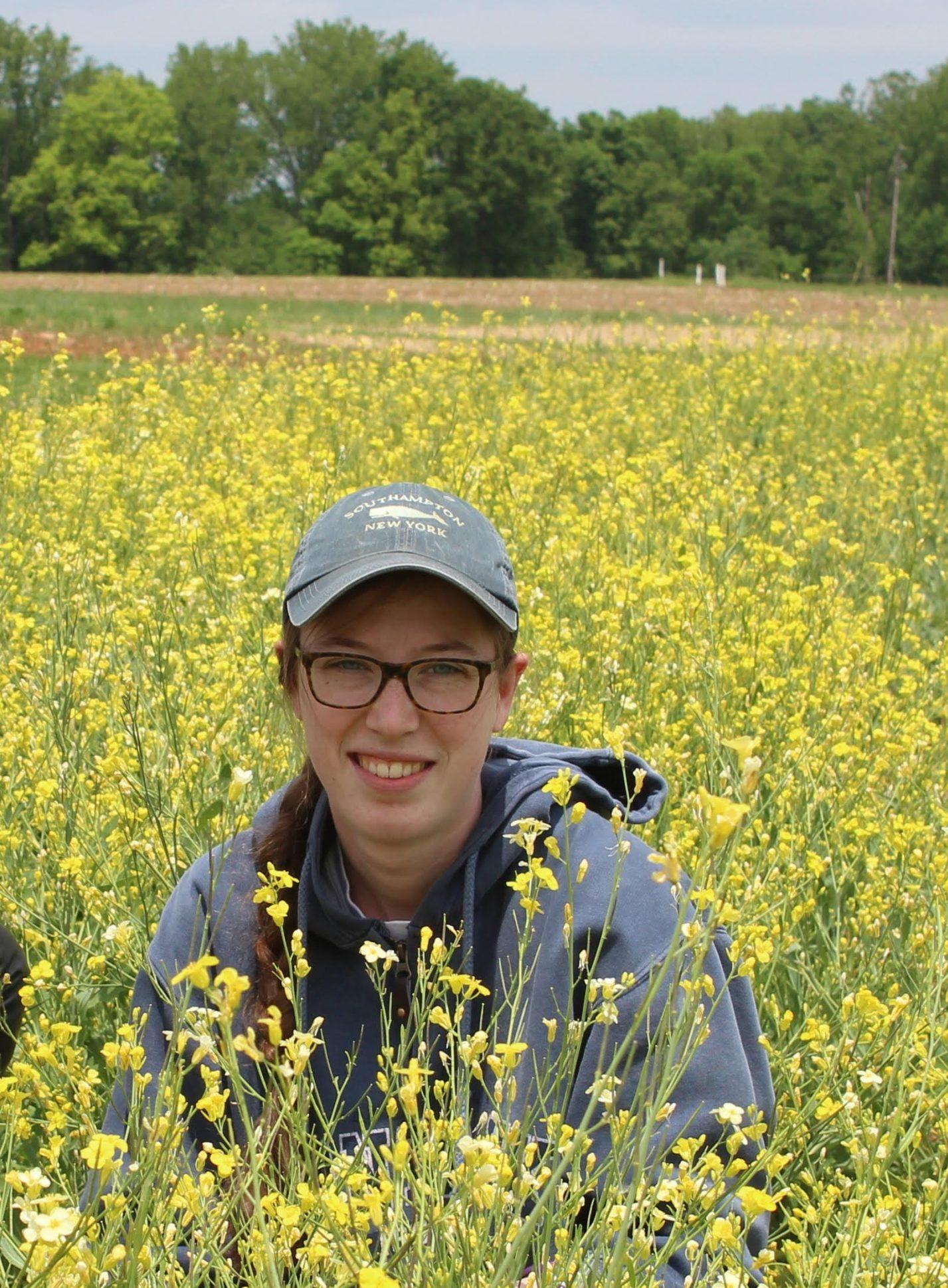 Woman in a blue hat kneels in a field of yellow flowers