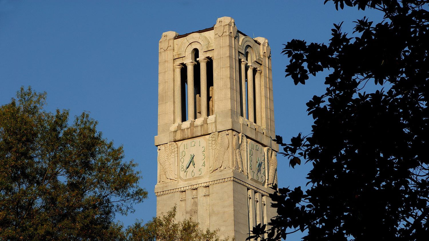 Sun sets on the Belltower under a crisp blue fall sky.