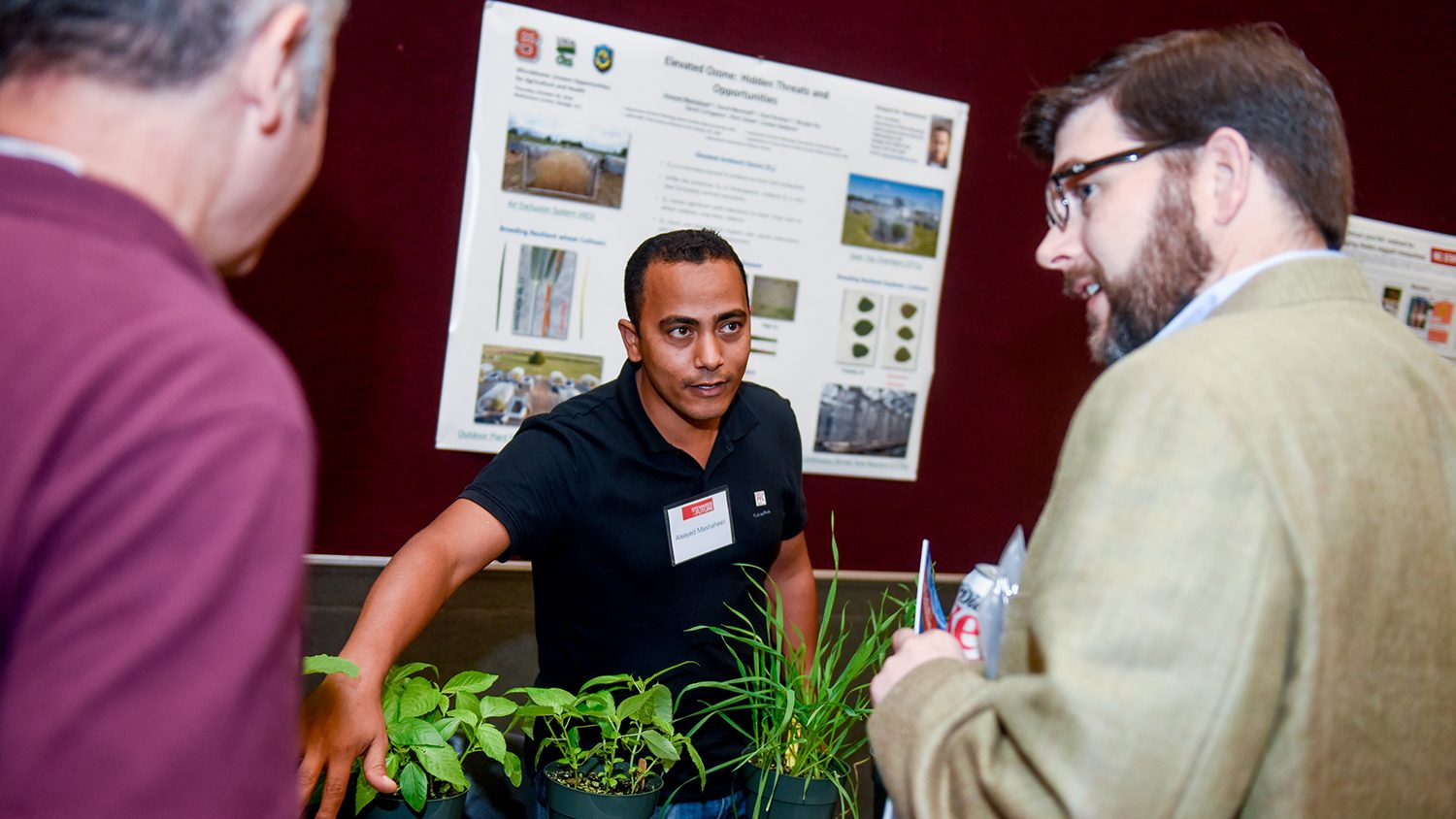 Scientist with plants explaining research to two onlookers.