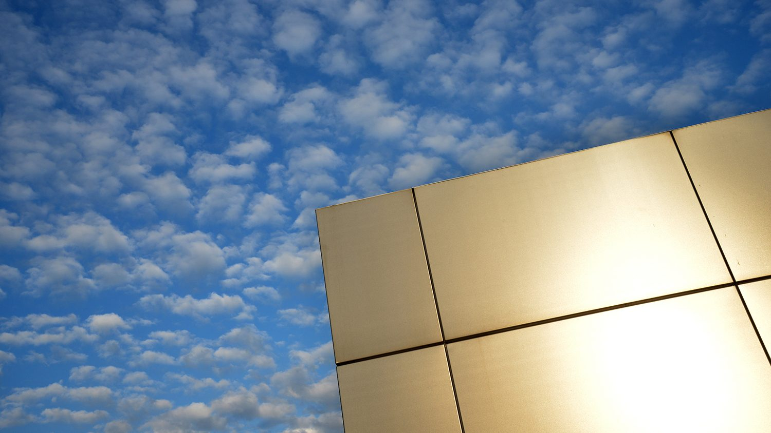 One corner of the Centennial Gateway against a cloud-filled sky