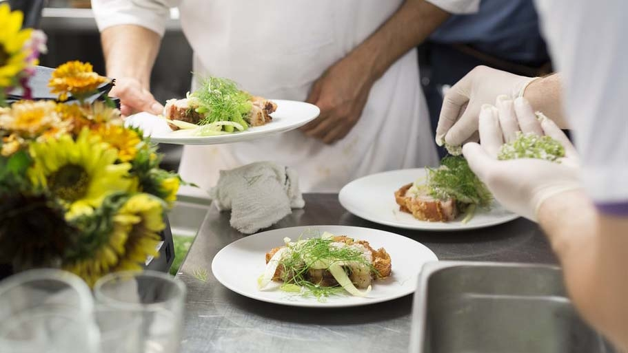 Hands plating food.