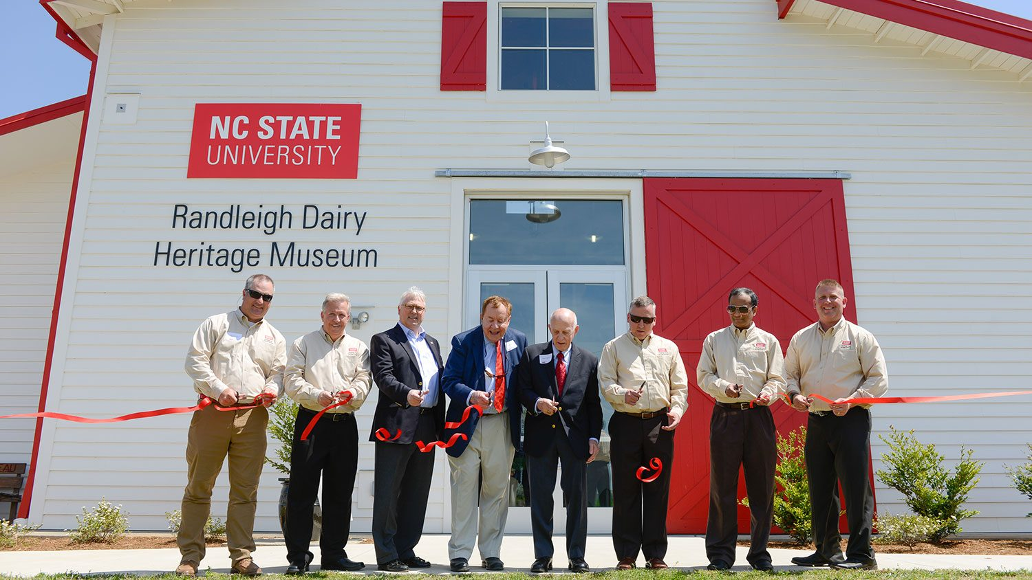 Group cutting ribbon in front of Randleigh Dairy Heritage Museum