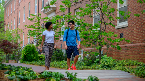 Two students walking by dorms