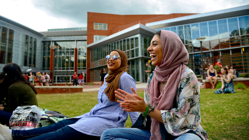 Students laughing while sitting on lawn in front of Tally Student Union