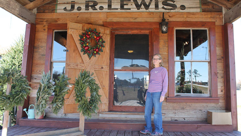 Woman standing in front of the door to her farm store.