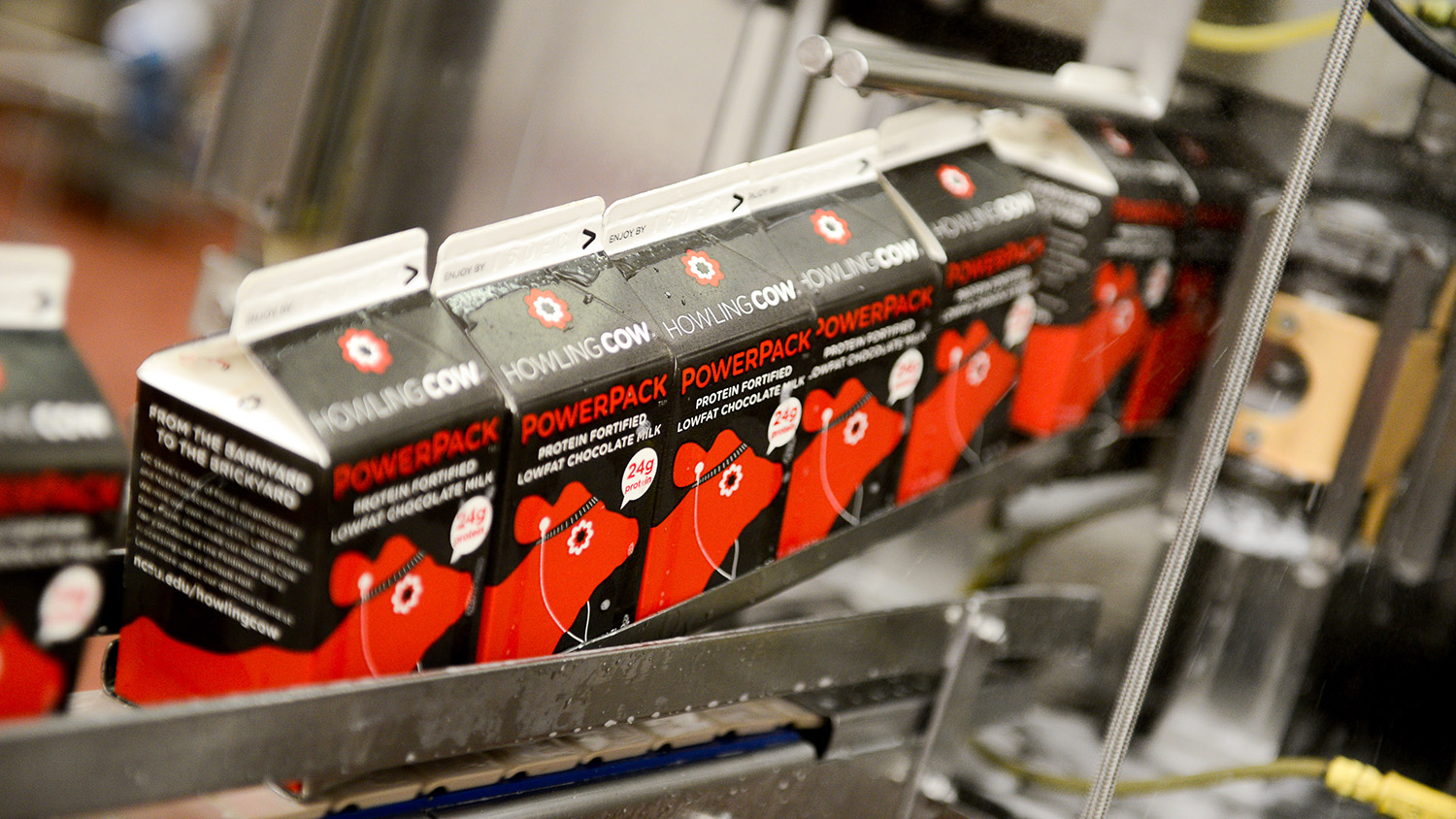 Cartons of PowerPack travel through the packaging process in an NC State food processing facility.