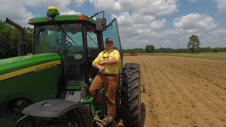 Student standing beside tractor.