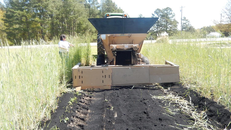 Tractor in a field, spreading black biochar in a 10-foot row.