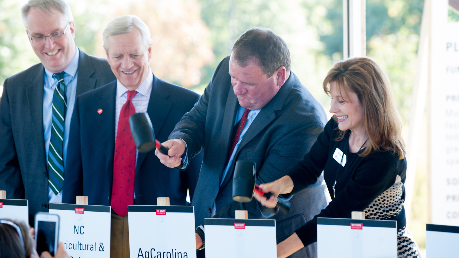 Four stakeholders, pounding stakes into the ground with rubber mallets