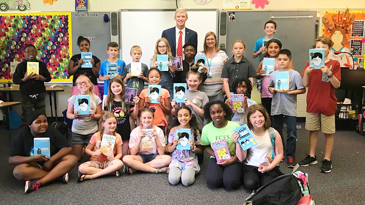 Class of elementary school students holding up books
