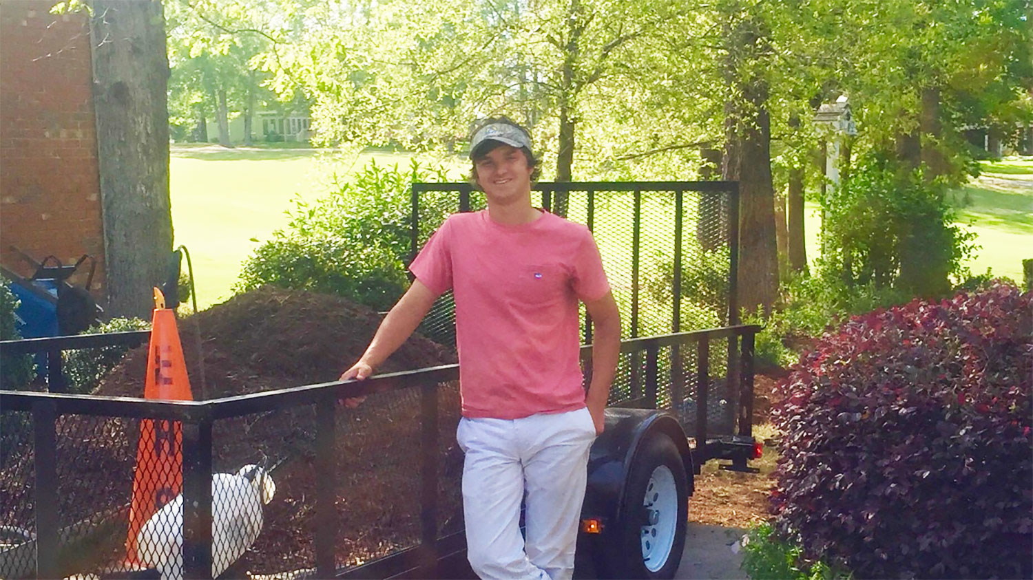 young man standing in front of a landscaping trailer