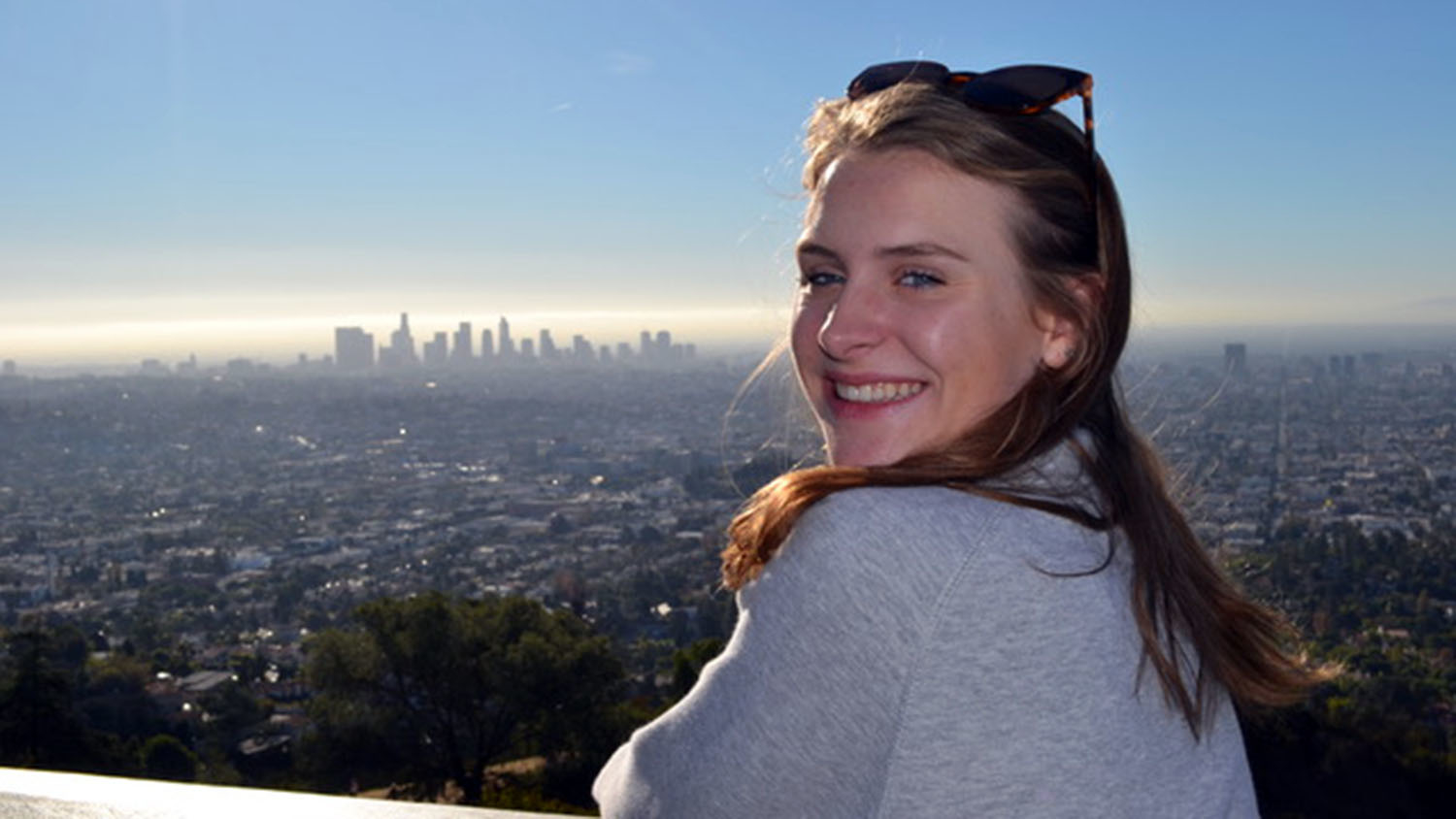 A high school girl looks back over her shoulder with a skyline in the background.