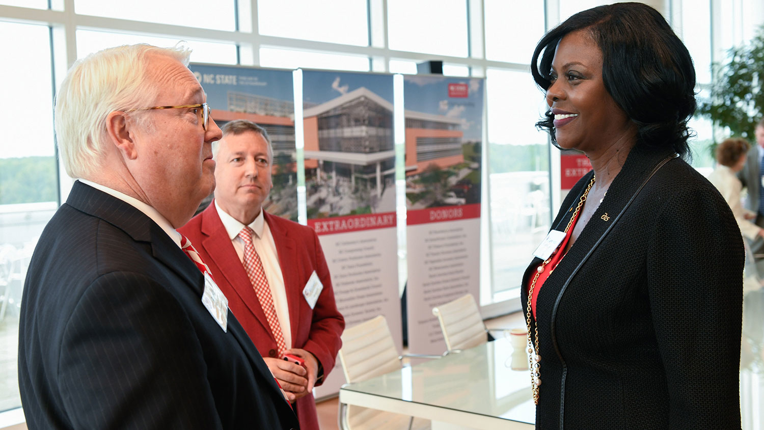 Chancellor Randy Woodson, Dean Richard Linton and USDA ARS Administrator Chavonda Jacobs-Young talking near a Plant Sciences Building display