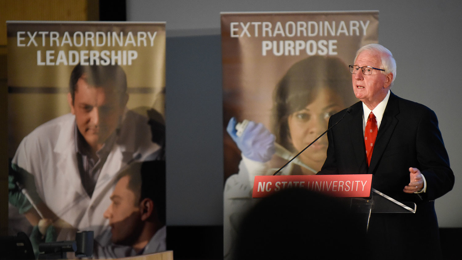 """Man at podium with banners behind him that say """"Extraordinary Leadership"""" and """"Extraordinary Purpose"""""""