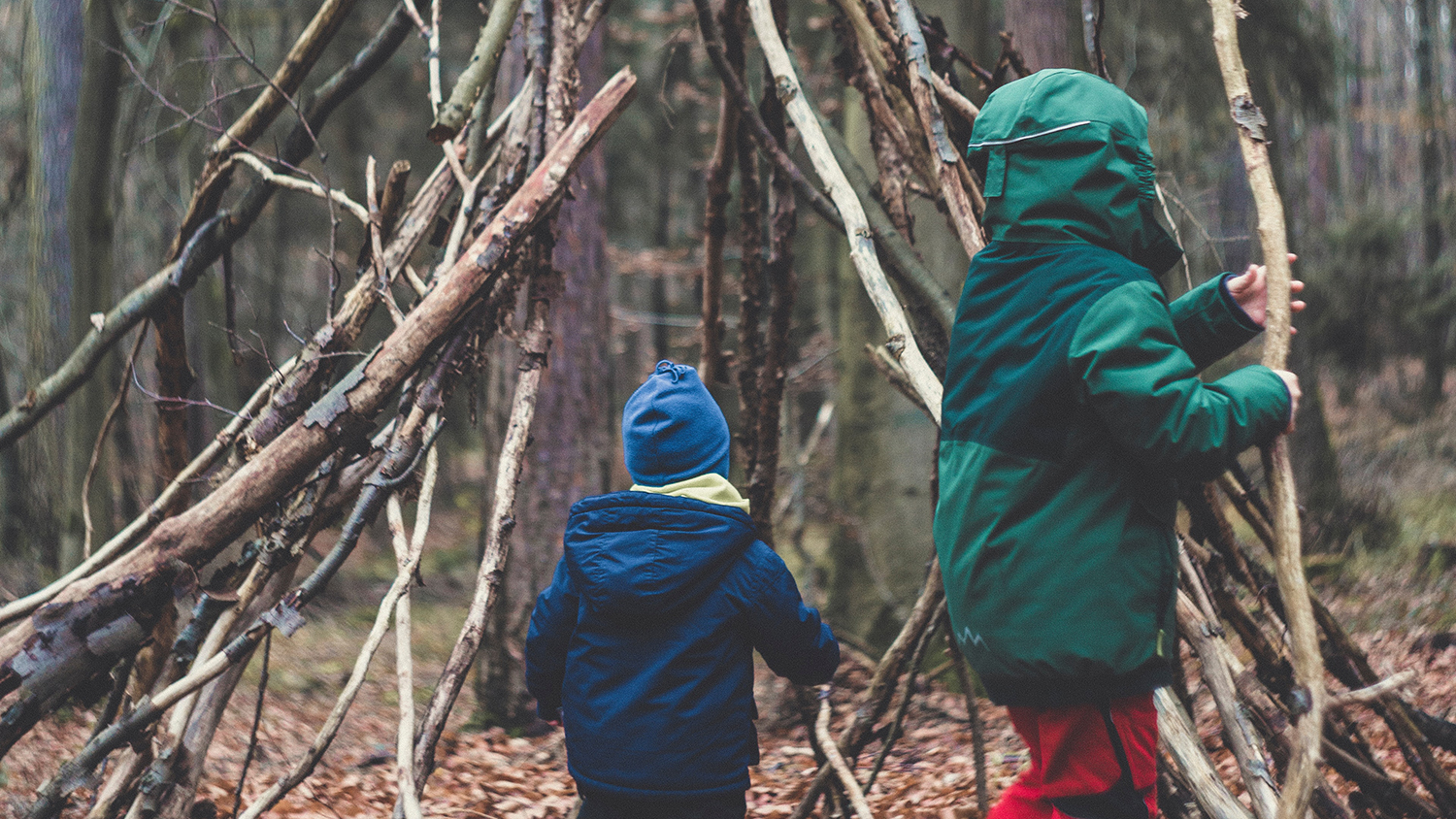 Two children building a stick structure in the woods