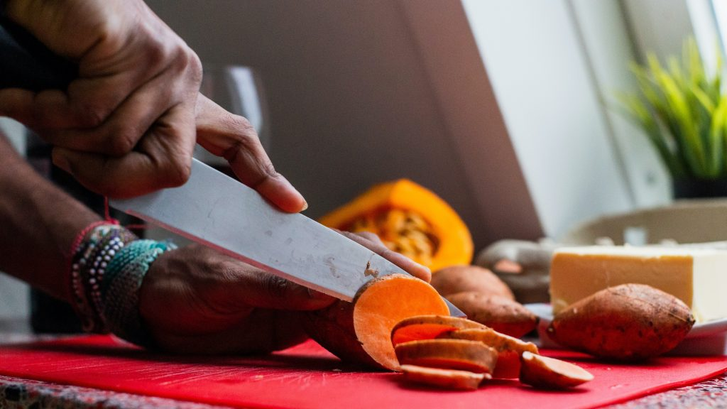 Hand with knife slicing a sweetpotato