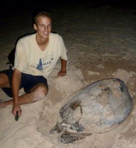 Andrew Maurer posing with a Hawksbill as it just finished laying its eggs and starts to cover the hole with sand.
