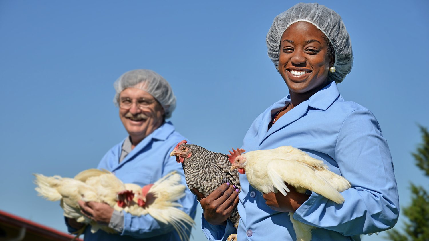 student and researcher holding chickens