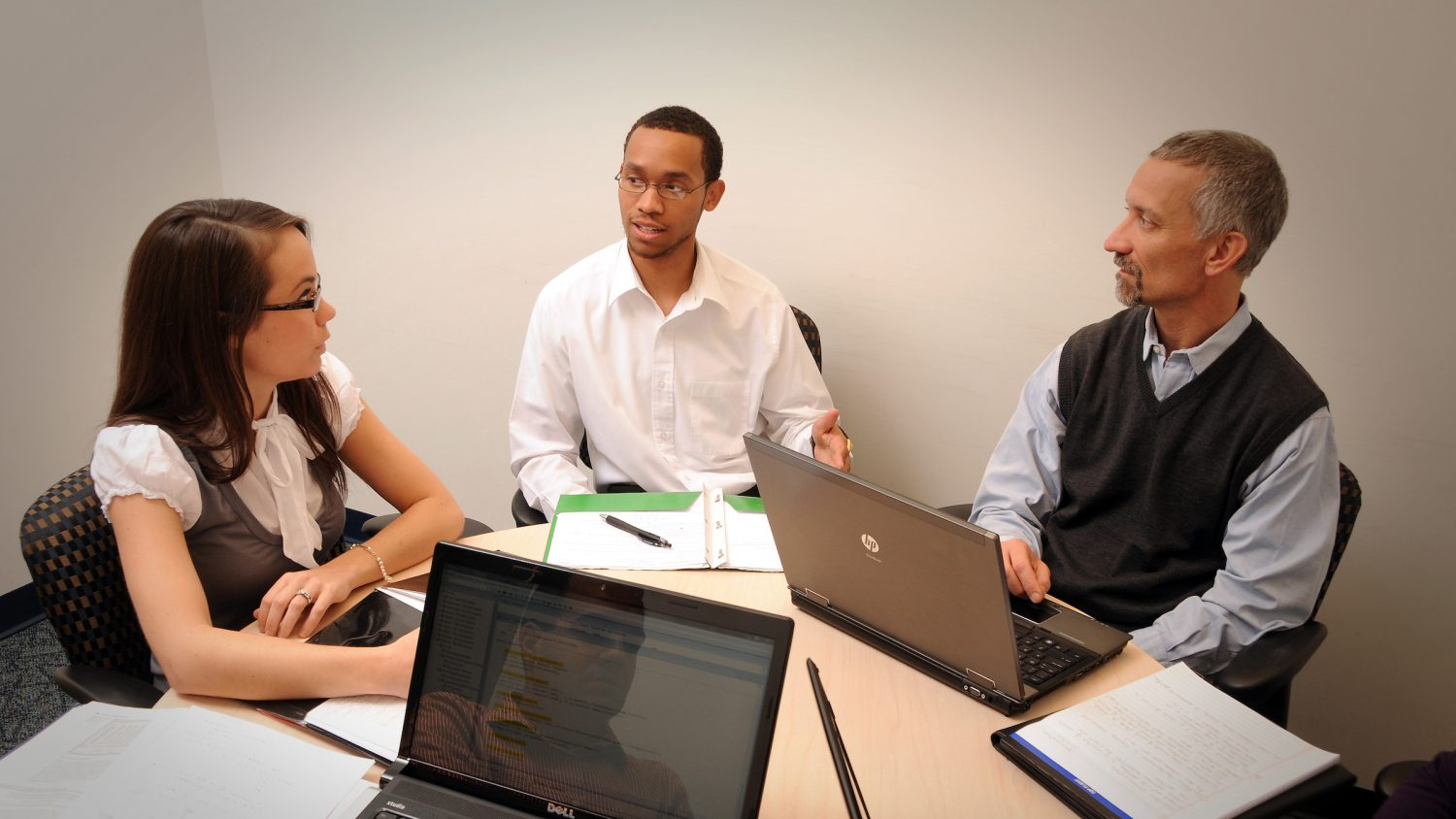 Three people in a meeting room