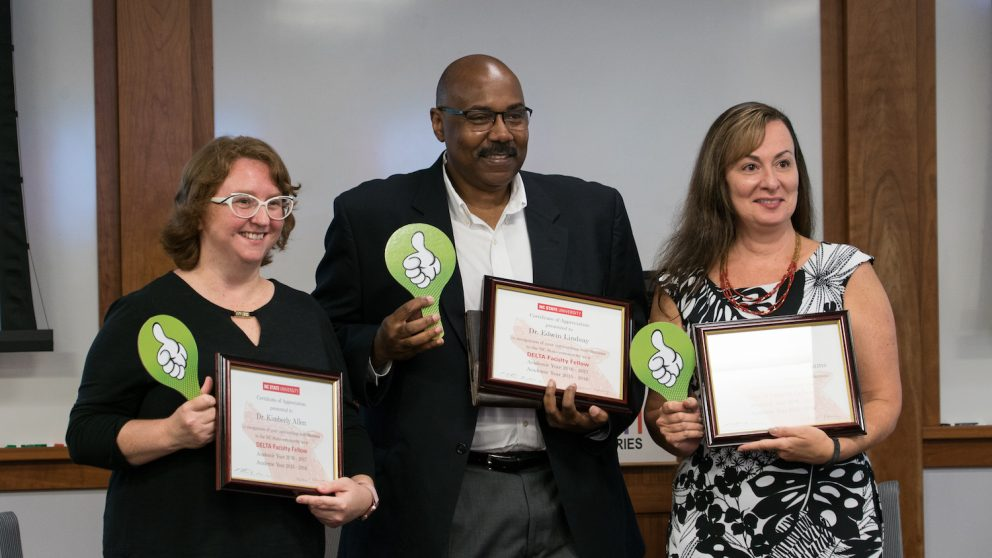 Photo of three faculty members holding framed certificates and thumbs-up signs.