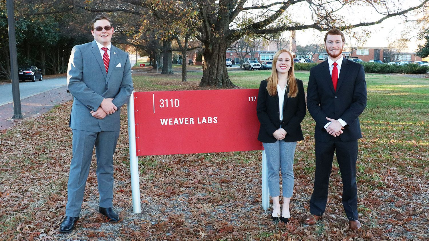 NC State students Matthew Parker, Lauryn Kabrich and Alex Greeson with the Weaver Labs sign.