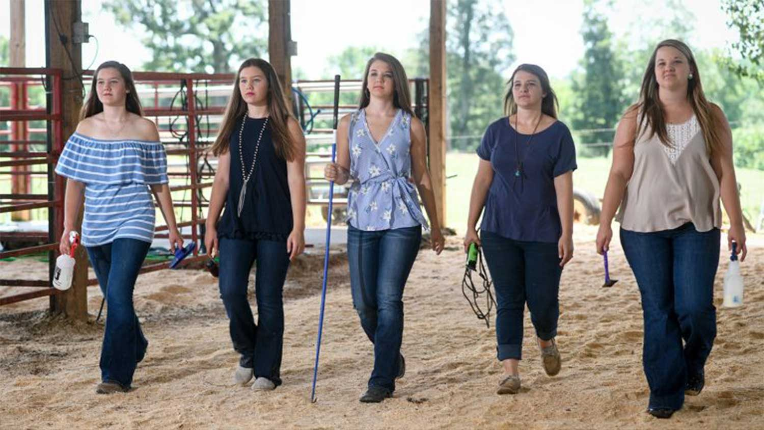 Five females walking with purpose in a barn