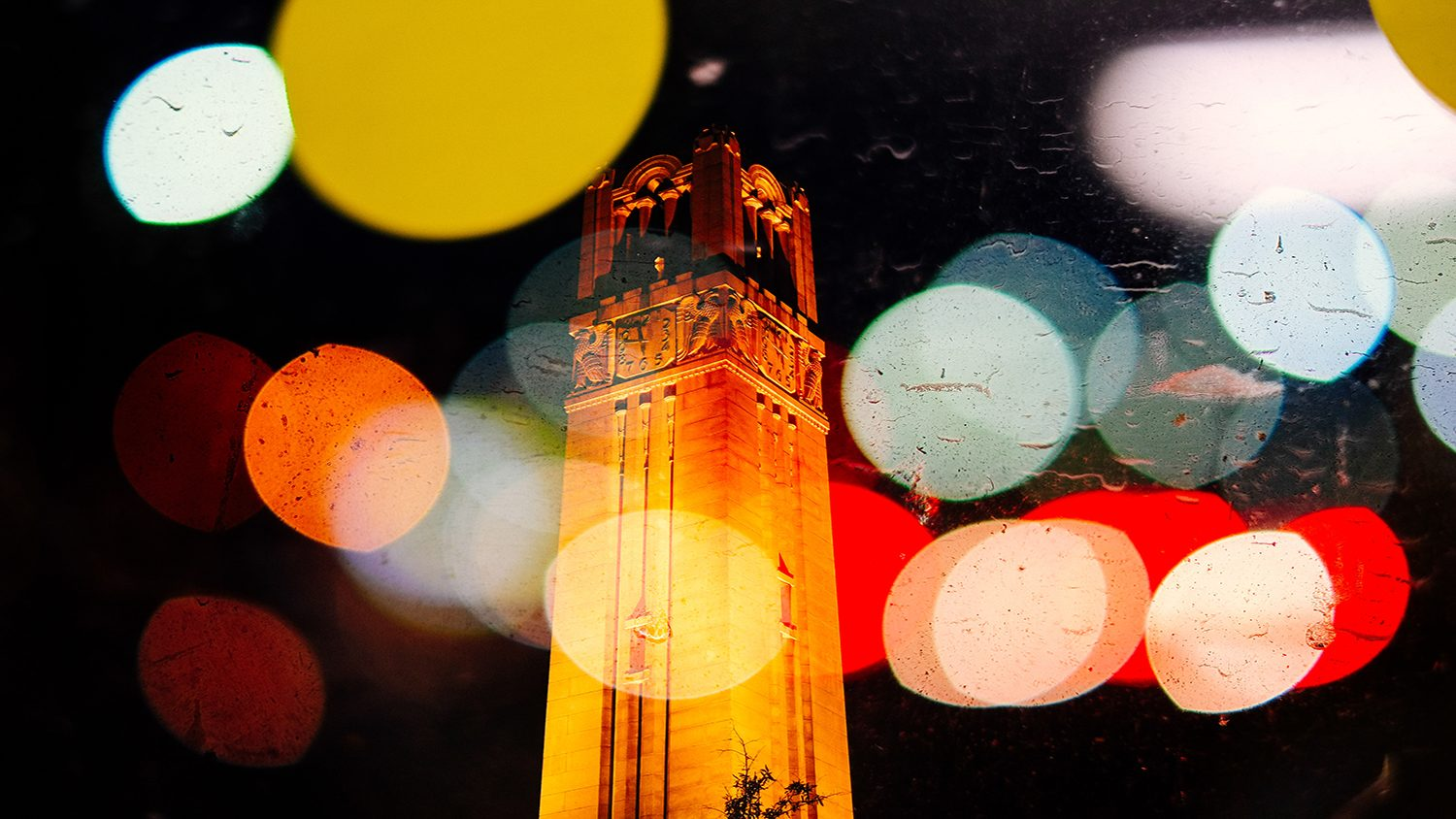 NC State Belltower at night with a glowing spotlight effect