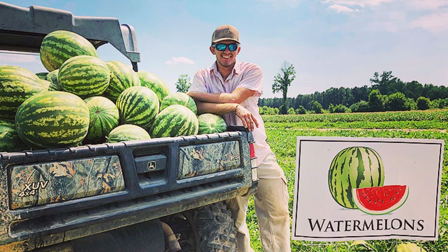 Man leaning on the back of a truck full of watermelons.