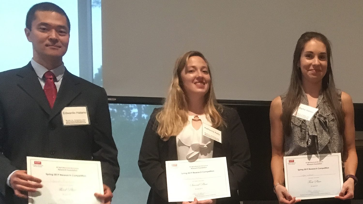 Pictures of two women and one man holding certificates.