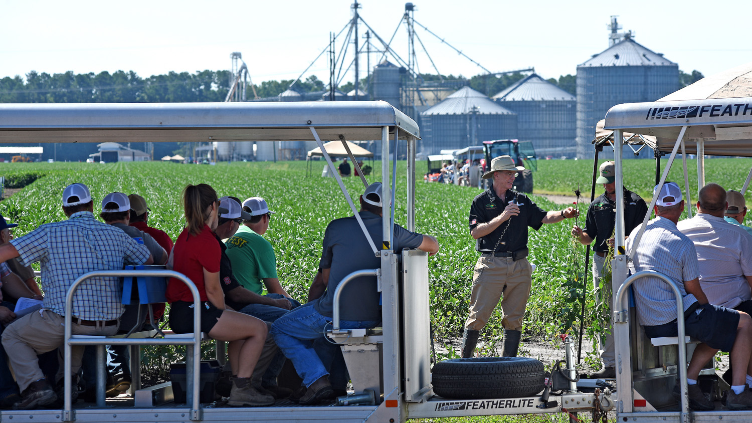 Extension specialist giving a field demonstration in a soybean field while onlookers in a tram observe.