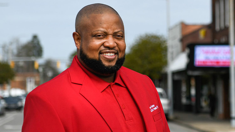 Black man in cheery red blazer.
