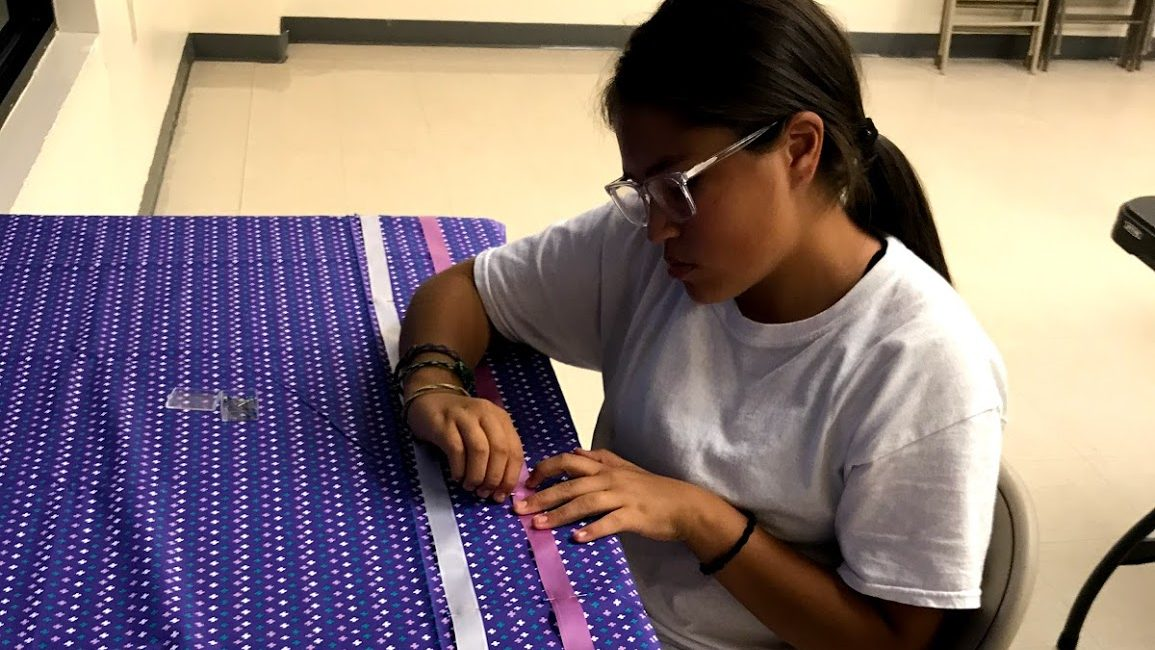 Young girl sews ribbon on traditional cherokee skirt.