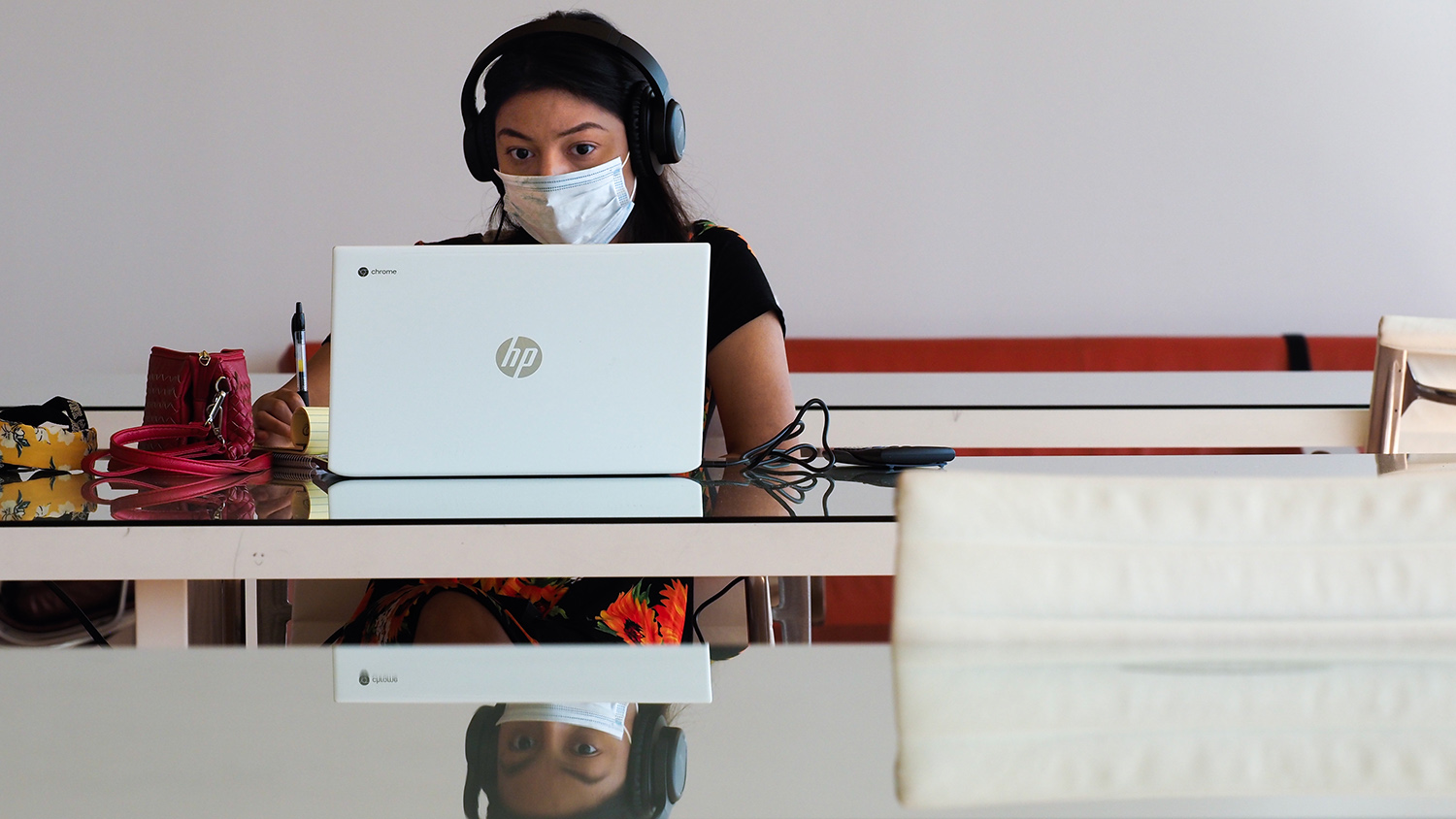 Woman with mask on working on laptop