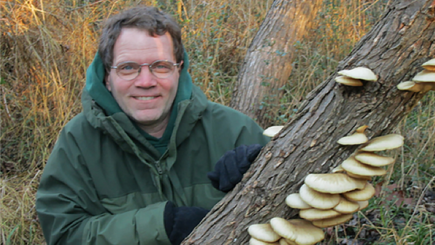 Man holding log with fungi