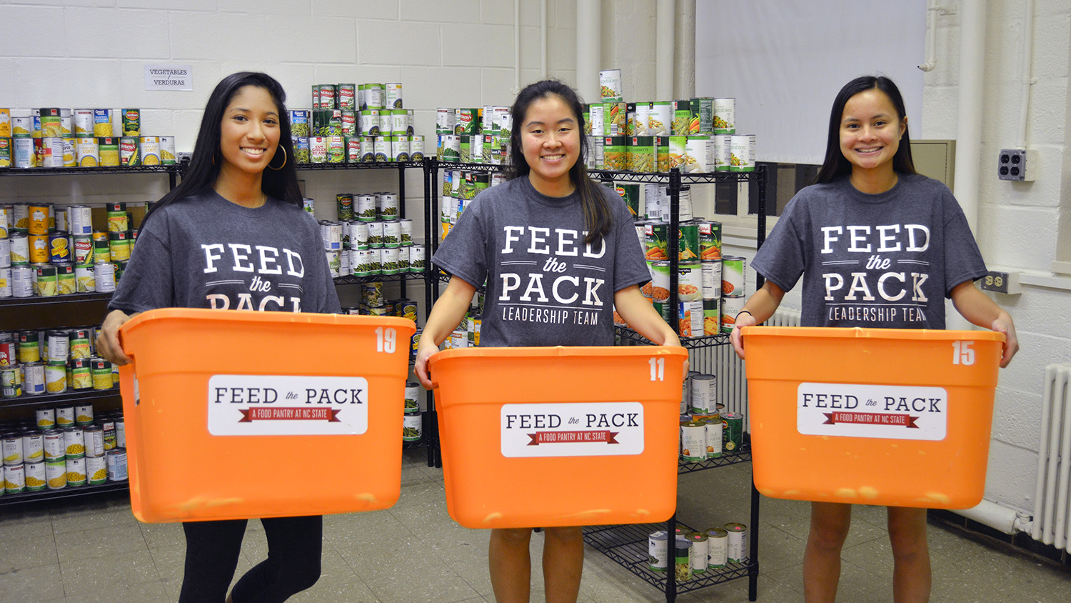 Three female students holding food collection bins