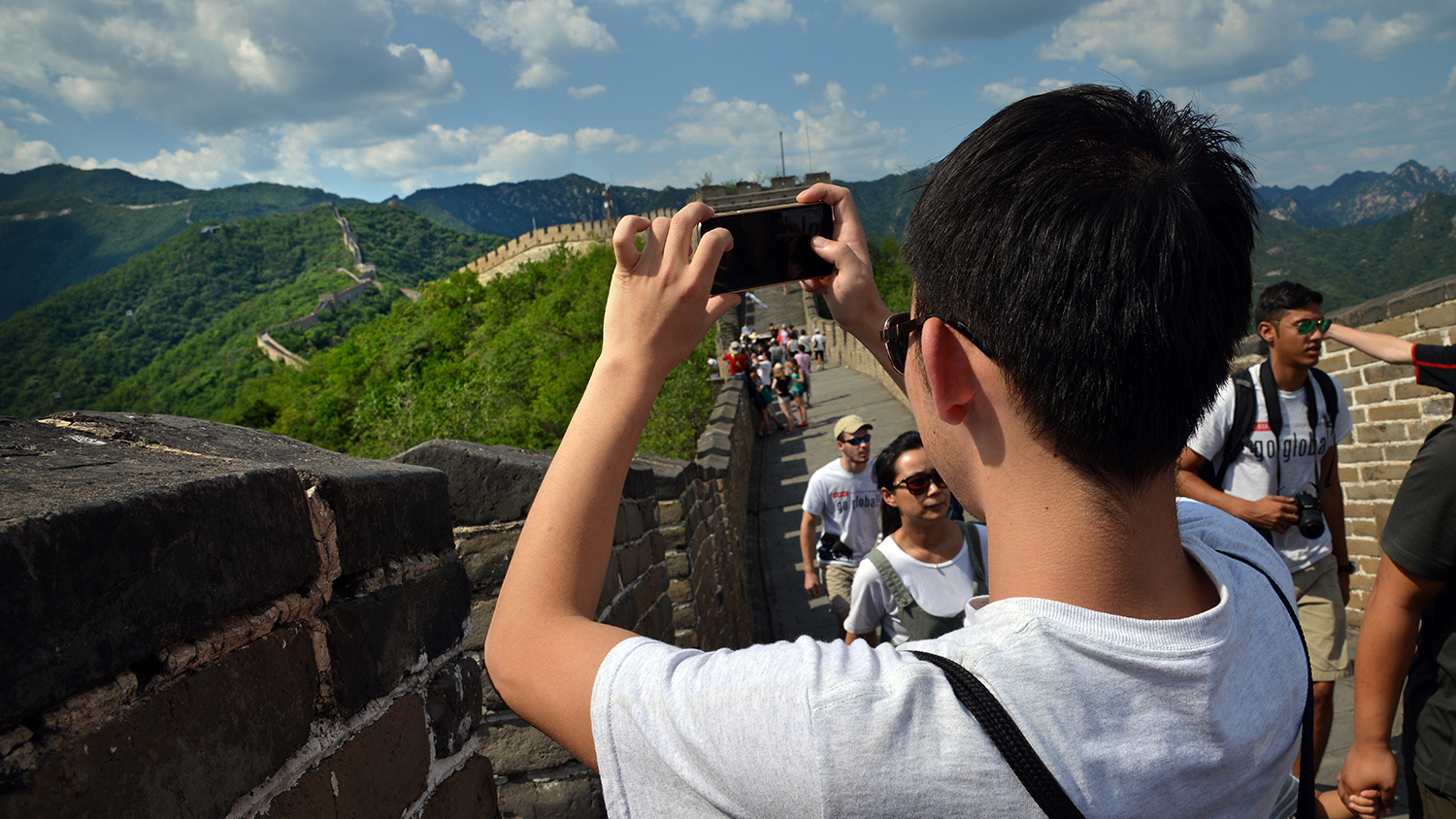 Back of man using his cell phone to take a photo of the Great Wall of China