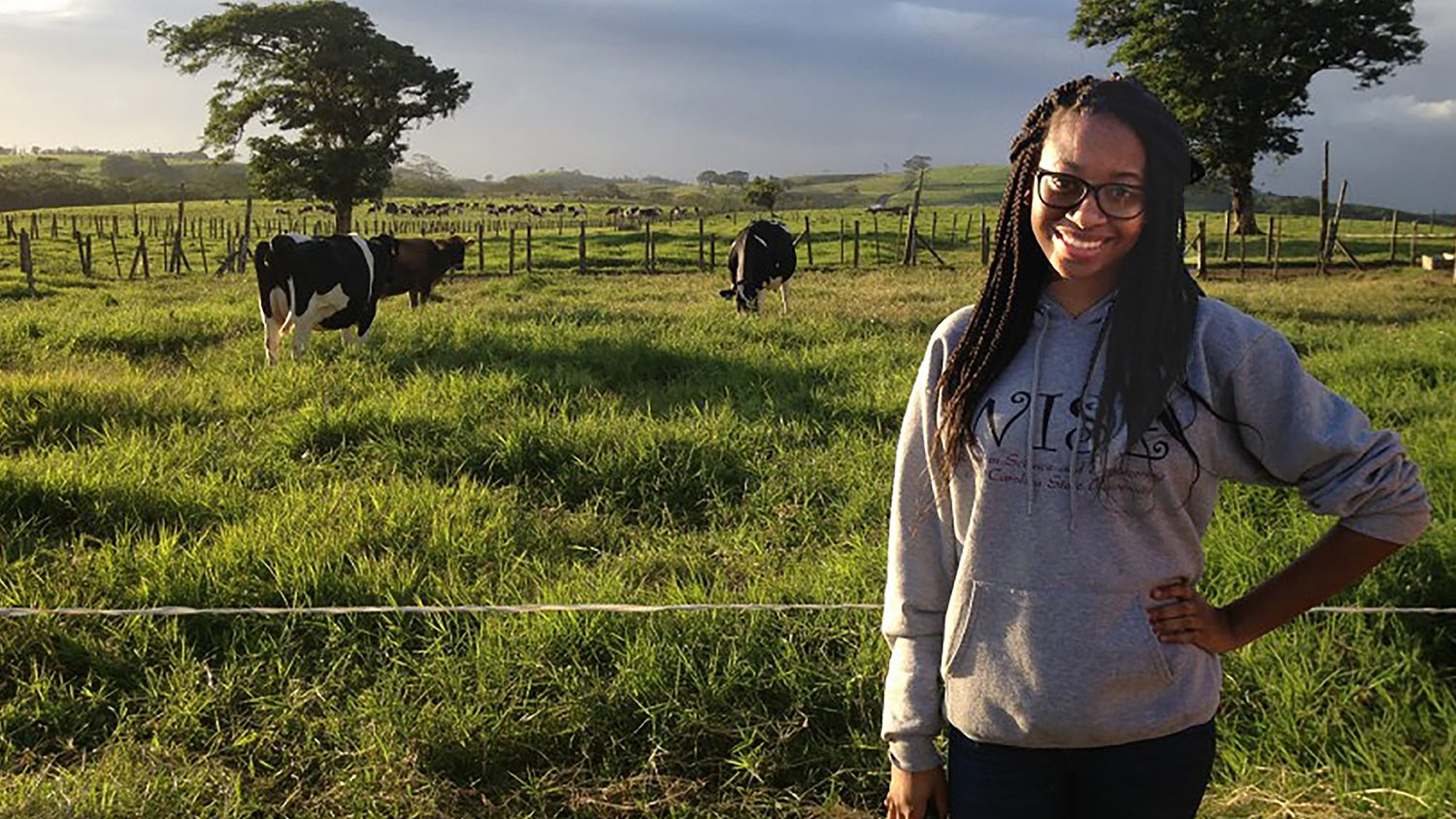 CALS student Nashea Williams standing in front of cows in a field.