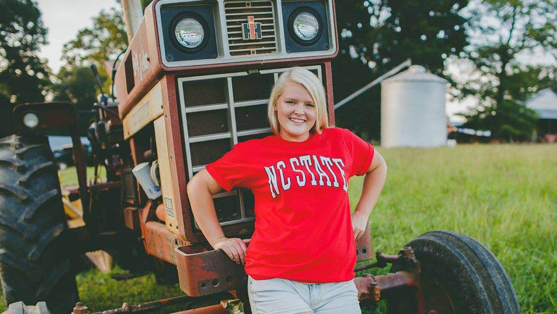 Bone scholar Laura Johnson standing in front of tractor.