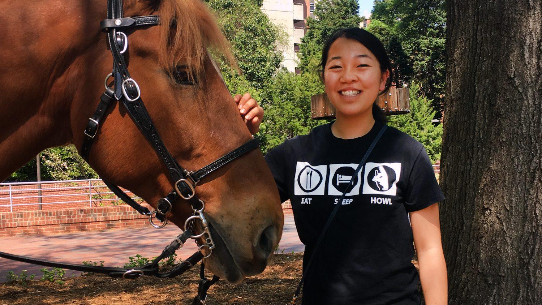 Prestage student Kristen Hasegawa petting a horse.