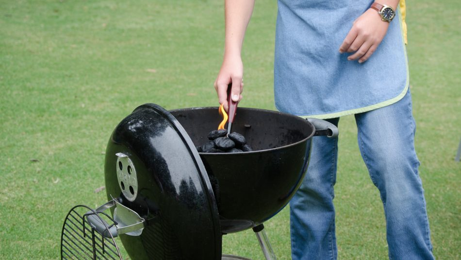 A griller lights charcoals in an outdoor grill