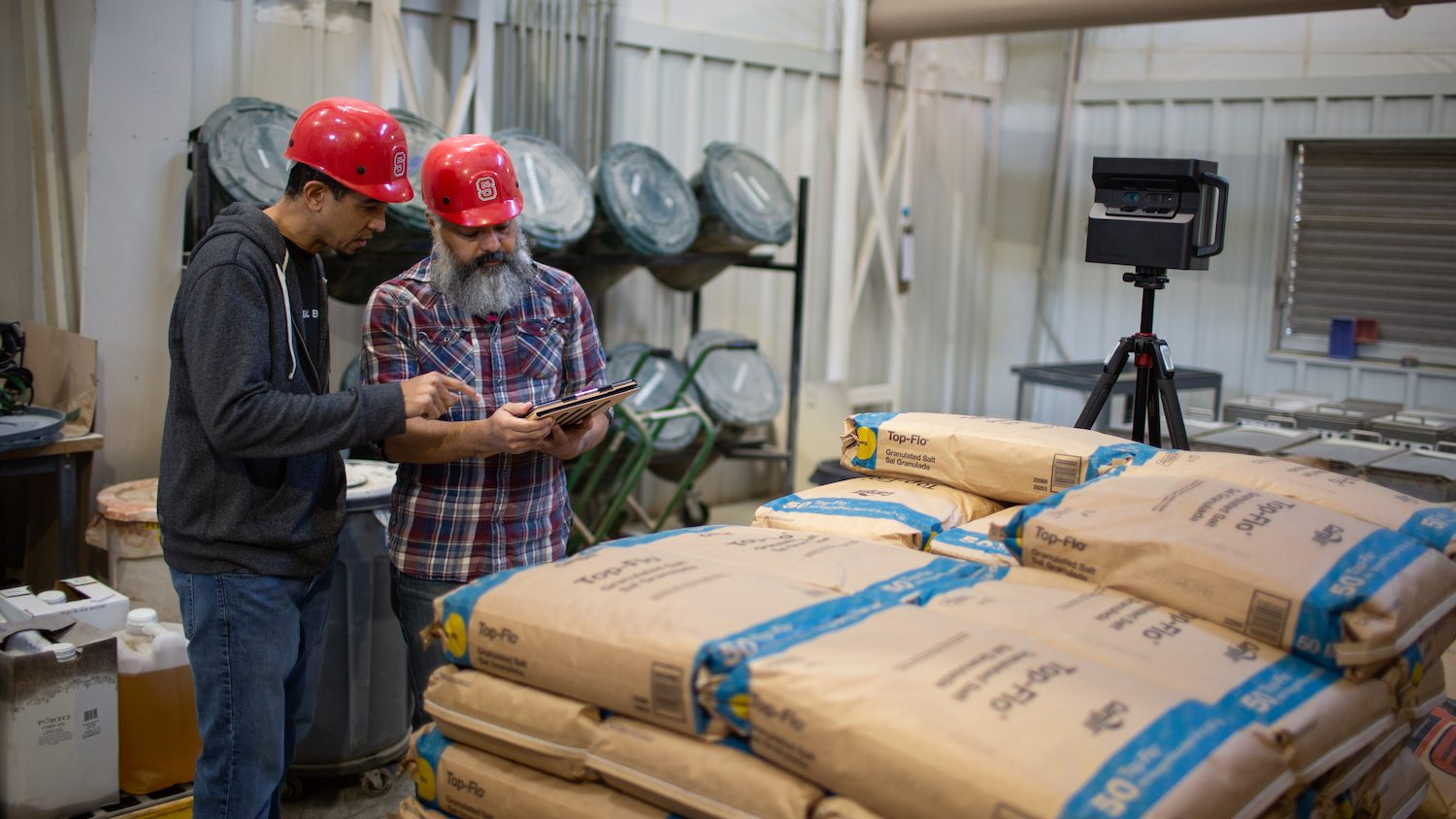 Two workers in red hard hats stand near stacked bags of animal feed