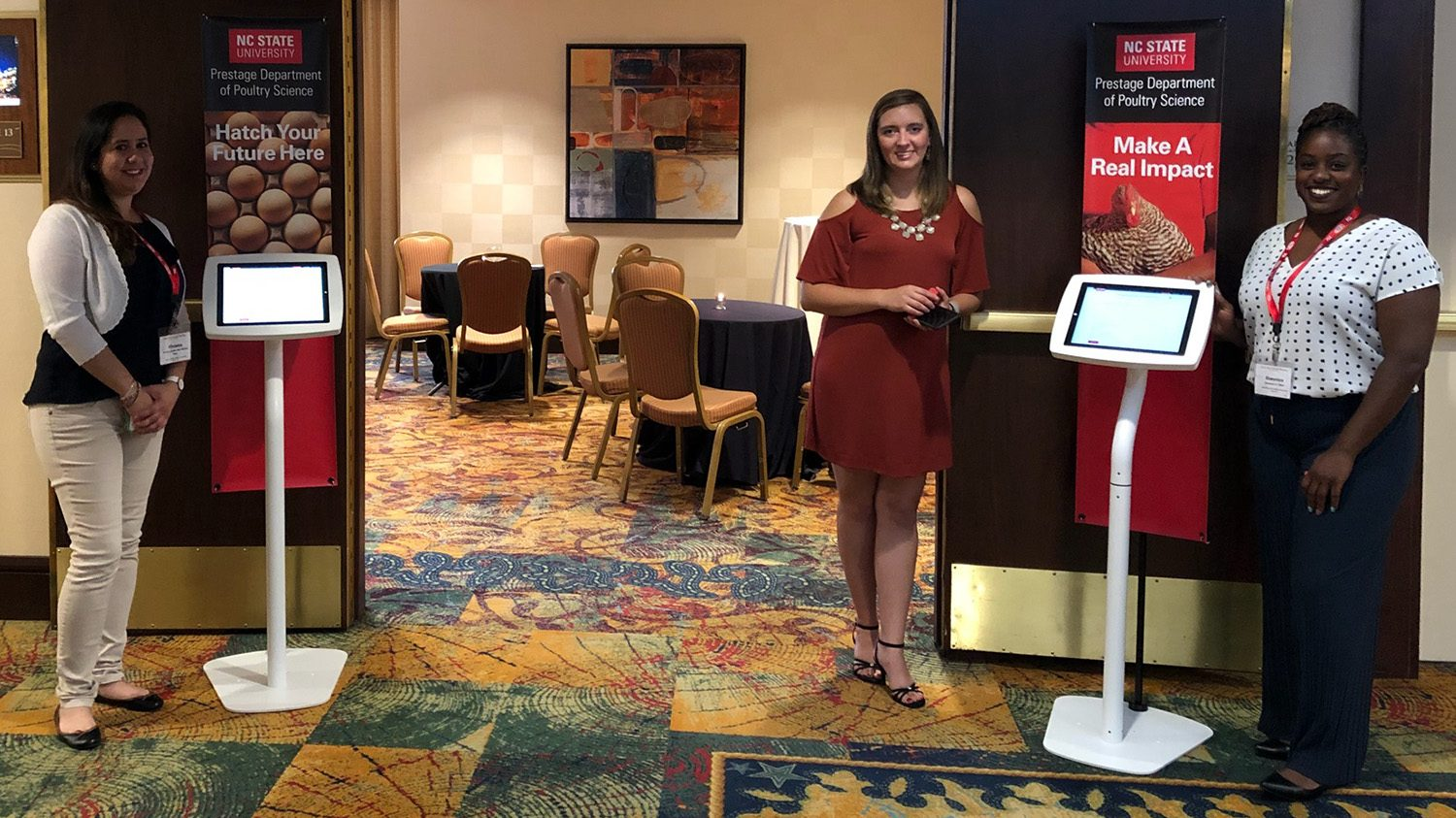 Three women and two kiosks in front of an open reception room