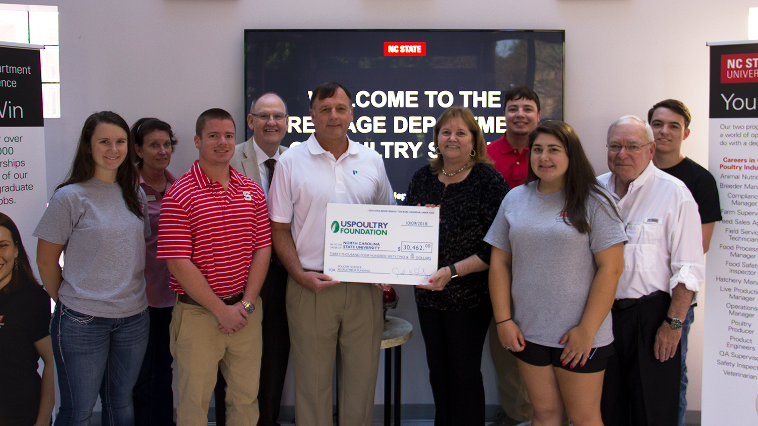 Group of PDPS and industry members hold a large donation check