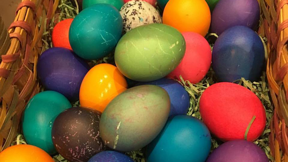 brightly colored eggs in a basket