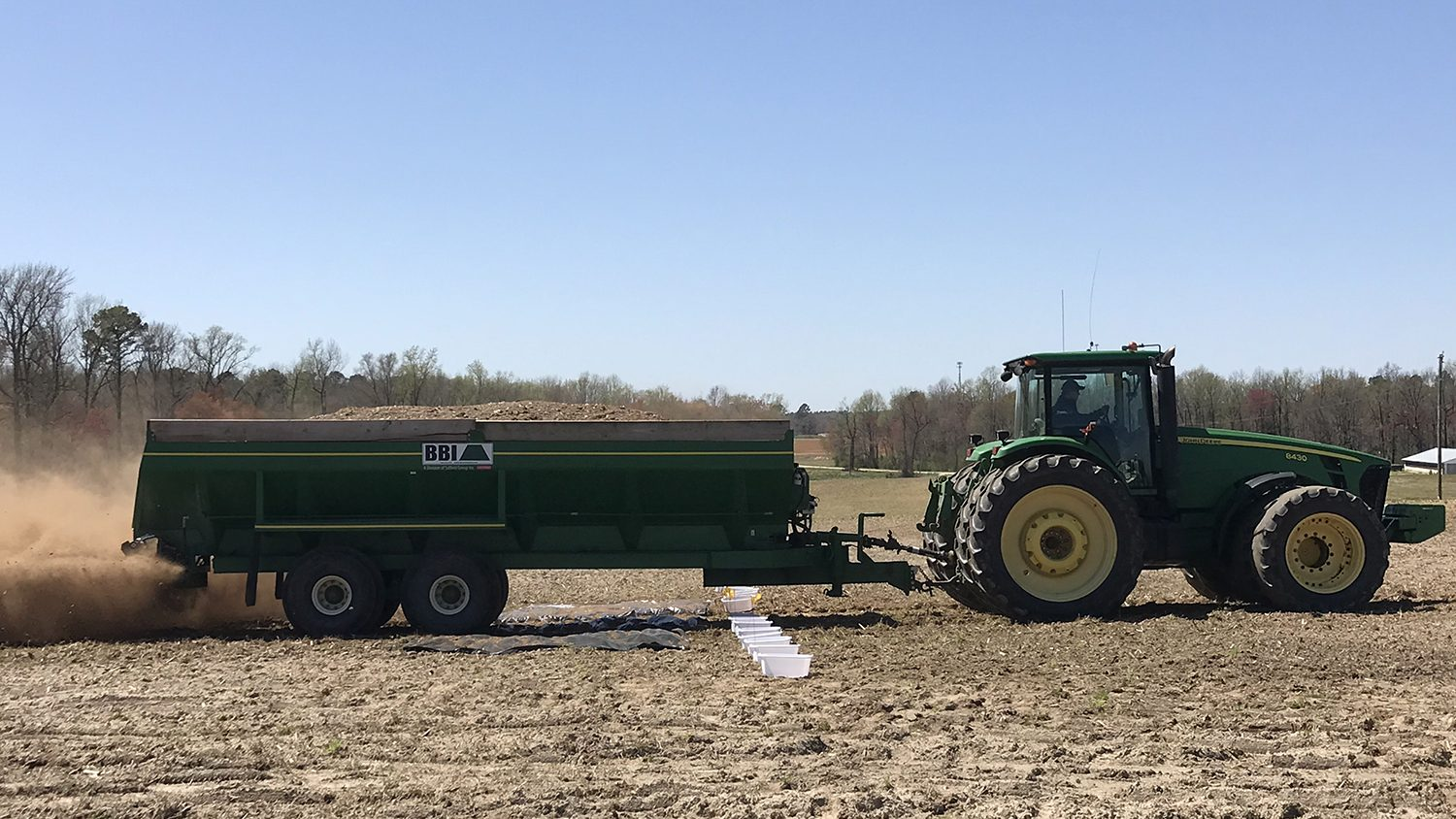 John Deere tracker pulling a litter spreader across a field